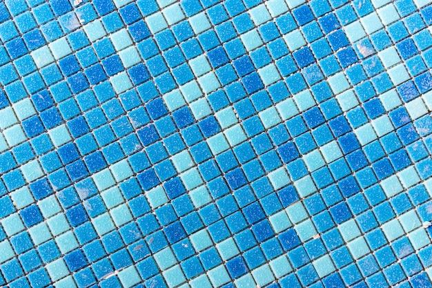 Голубая керамическая мозаика в бассейне. укладка мелкой плитки в бассейне. фон крупным планом. строительные работы в бассейне.