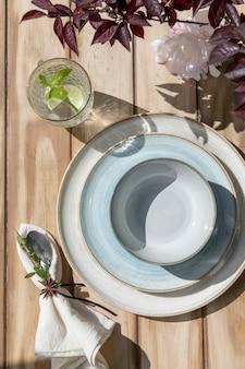 青いセラミックプレート、カトラリー、木製のテーブルにレモネードとガラス
