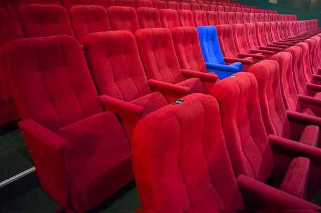 Синий стул между рядами красных сидений в современном театре. концепция киносцены