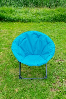 緑の芝生を背景にした青い長椅子。