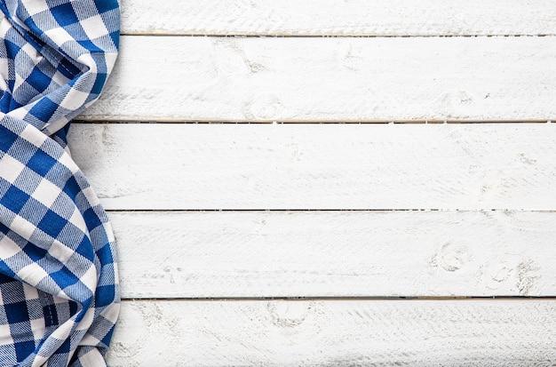 木製のテーブルに青い市松模様のキッチンテーブルクロス。