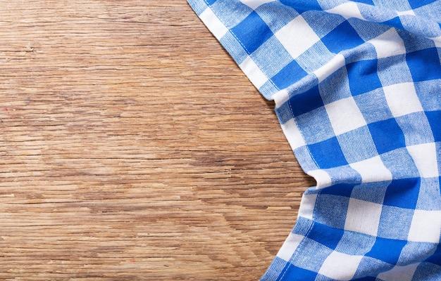 Синяя клетчатая скатерть на деревянном столе, вид сверху