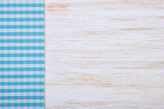 Blue checkered tablecloth textile on white wooden table background. top view, flat lay with copy space, banner