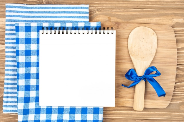 Blue checkered tablecloth and wooden appliances for cooking and baking. with copy space. horizontal.