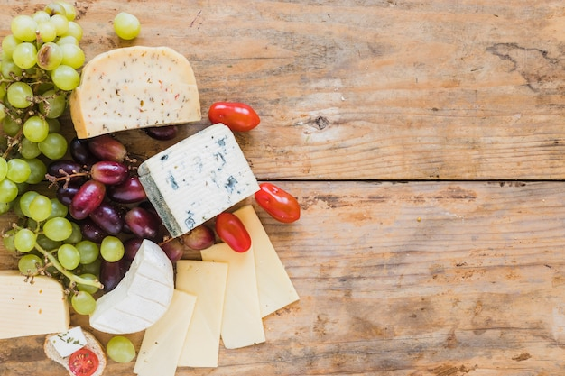 Blue cheese blocks and slices with grapes and tomatoes on wooden desk