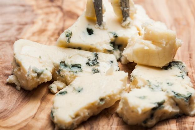 Голубой сыр крупным планом на оливковой деревянной доске