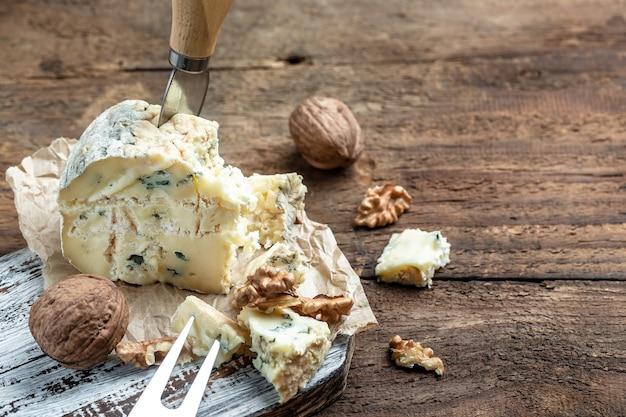 Дорблю с голубым сыром, горгонзола, рокфор с грецкими орехами на деревянных фоне. баннер, меню, место рецепта для текста.