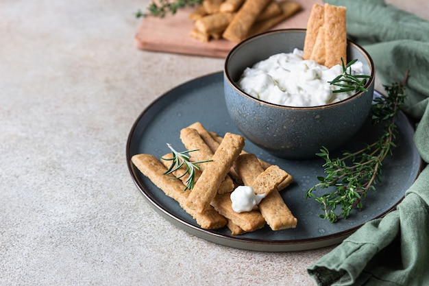 Blue cheese dressing or dip sauce with rosemary and gingerbread cookies sticks.