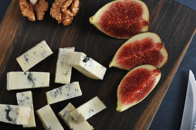 Blue cheese, fresh figs and walnuts on a wooden board and a knife and fork