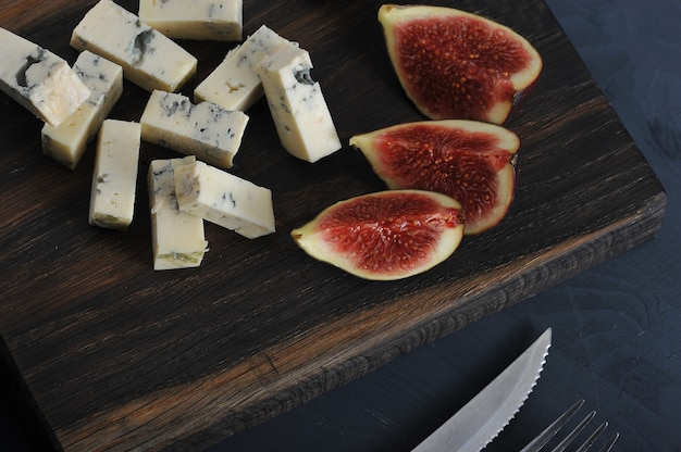 Blue cheese, fresh figs on a wooden board and a knife and fork