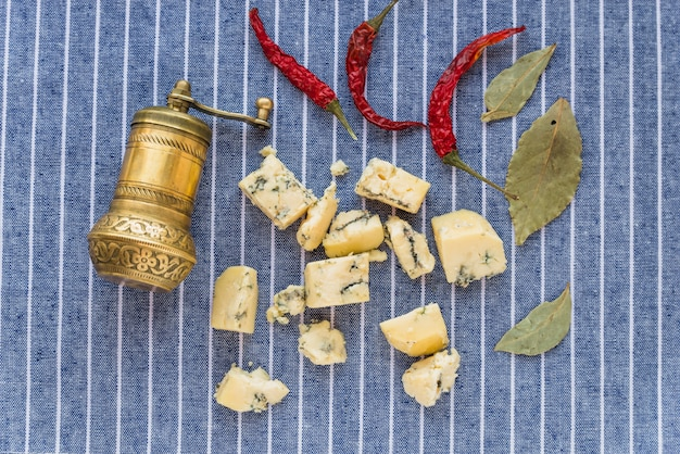 Blue cheese near dry red pepper and leaves