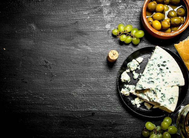 블루 치즈, 올리브와 검은 나무 테이블에 흰 포도.