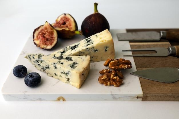 Голубой сыр на сырной доске с инжиром, грецким орехом и черникой на белом фоне