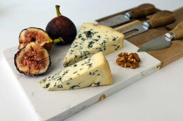 Голубой сыр на сырной доске с инжиром грецким орехом на белом фоне