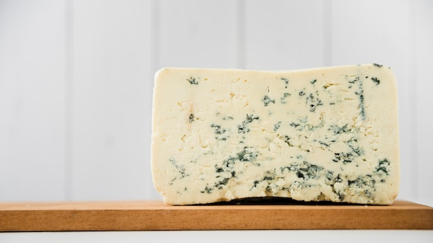Blue cheese piece on wooden chopping board over white desk