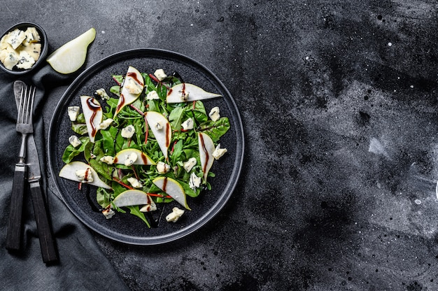 Blue cheese salad with , pears, nuts, chard and arugula. black background. top view. copy space