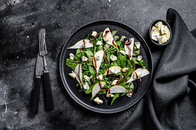 Blue cheese salad with , pears, nuts, chard and arugula. black background. top view