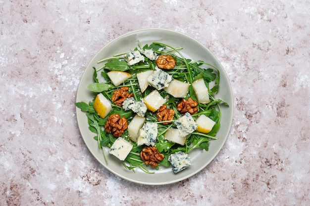 Blue cheese salad with walnut and ruccola and olive oil and pear slices