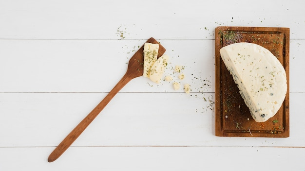 Blue cheese and spatula on wooden chopping board over white desk