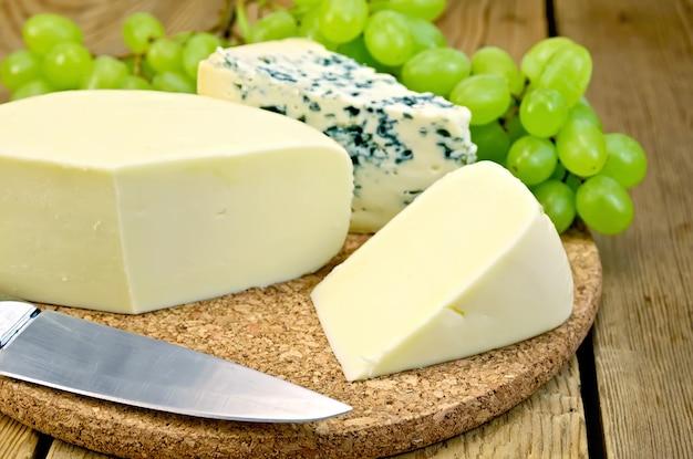 Голубой сыр, сулугуни, виноград, нож на деревянной доске фона