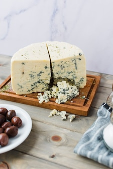 Blue cheese with olives on wooden desk