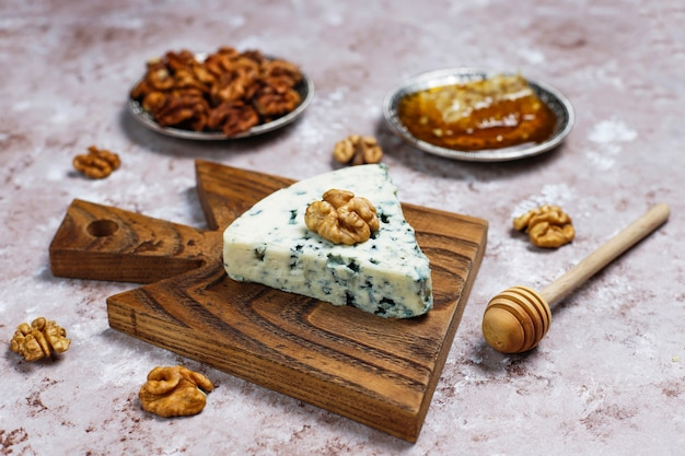 Blue cheese on wooden cutting board with honey and walnuts
