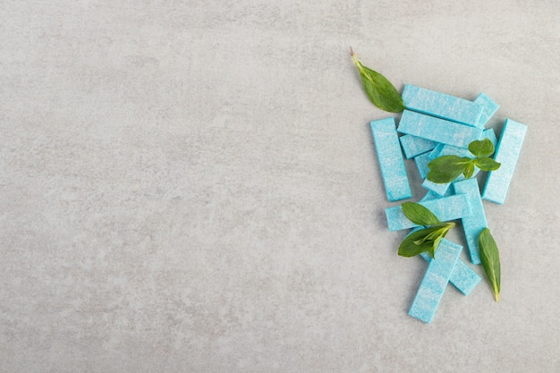 Blue chewing gums with mint leaves placed on a stone table .