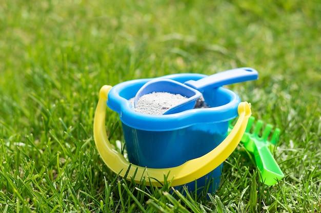 緑の草の中に緑の熊手が付いている青い子供プラスチックのおもちゃのバケツ。