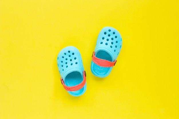 Blue children's rubber sandals on yellow background.