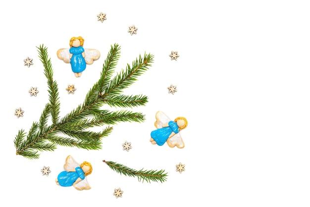 Голубые рождественские ангелы и еловые ветки на белом фоне.