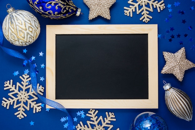 Blue christmas background, mock up. top view ofwinter silver decorations around chalckboard. copy space.