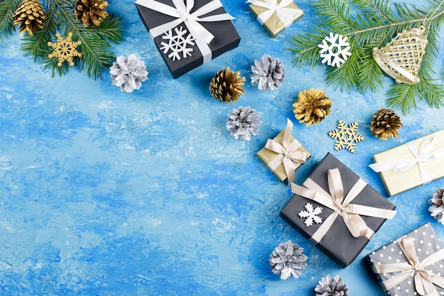 Blue christmas background with fir branches, giftboxes, silver and golden decorations, copy space. top view