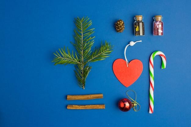 モミの木の枝、キャンディー、紙吹雪、ハート、コーン、シナモンとガラス瓶と青いクリスマスの背景。フラットレイスタイル。今年の色。