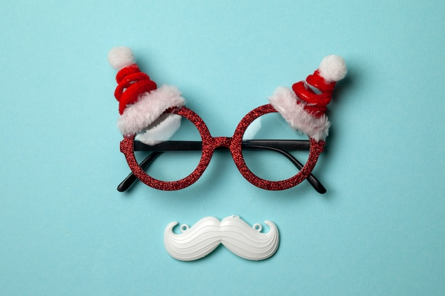 Blue christmas background with santa glasses and white hipster mustache.