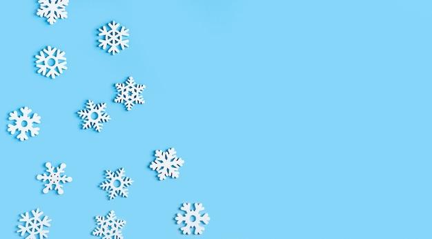 白い雪と青いクリスマスの背景。コピースペース付きフラットレイポスター。正月、冬