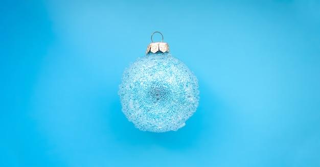 Синий рождественский шар с некоторыми шишками на синем фоне минималистичный рождественский дизайн место для текста