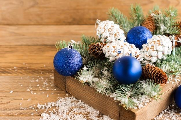 素朴なスタイルのテーブルにトウヒの枝が付いている木製の箱の青いクリスマスボールと銀の円錐形。クリスマス作文。
