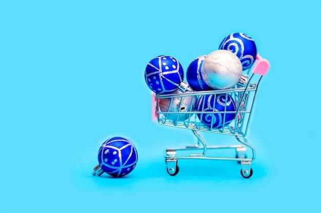 Синие новогодние шары сложены в небольшой тележке для покупок.