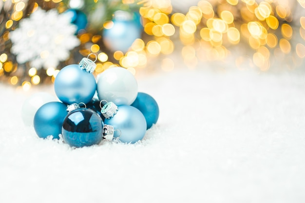 Blue christmas balls laying on the snow on the background of christmas tree