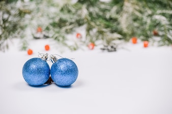 Blue Christmas balls on snow with fir branches