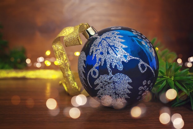 Blue christmas bauble with gold ribbon on wooden surface