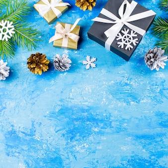 Синяя рождественская рамка с еловыми ветками, подарочными коробками, серебряными и золотыми украшениями, копией пространства