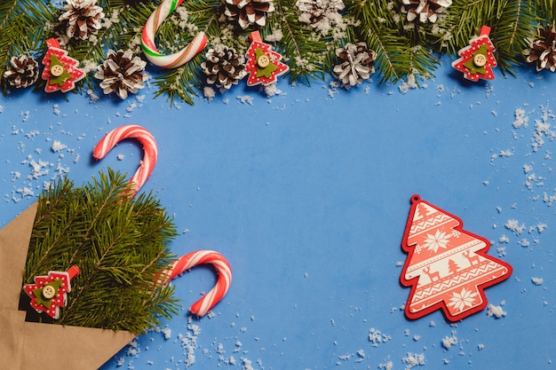 Blue christmas composition with fir branches, candy cane and cones