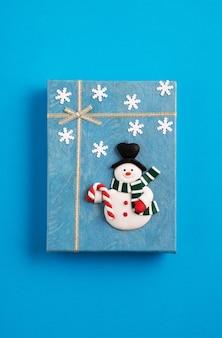 Синяя новогодняя подарочная коробка, украшенная снеговиком и снежинками