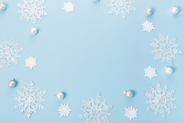 Blue christmas holiday composition. festive creative white pattern, xmas decor holiday ball with snowflakes on blue background. flat lay, top view