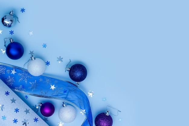 ブルークリスマスまたは年末年始フラットレイ。雪片とクリスマスリボンの周りの青、紫、白のクリスマスボール。