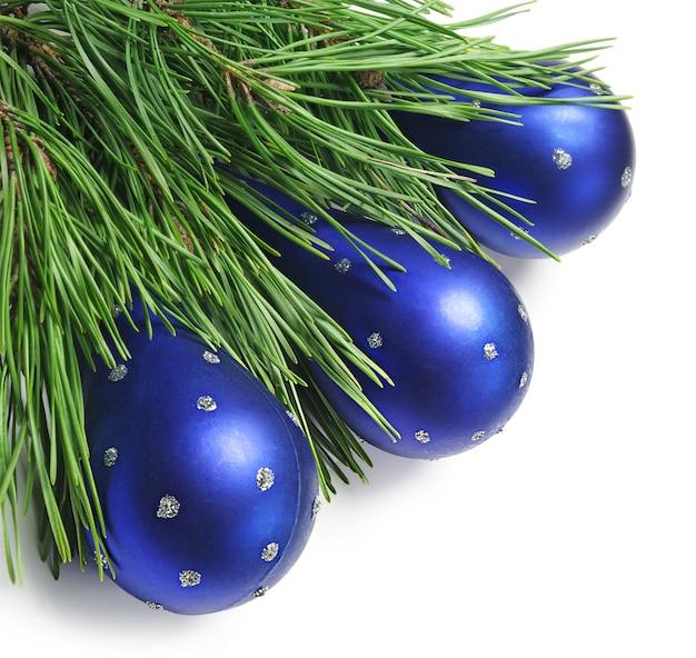 白い上の青いクリスマスのおもちゃと松の枝