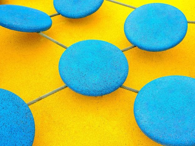 明るい黄色の背景にロープで接続された青い円。子供の遊園地の乗り物のマルチカラーのゴム引きコーティング。抽象的な背景。
