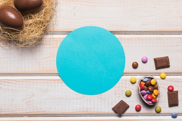 Blue circular frame with chocolates and easter eggs on nest over the wooden desk