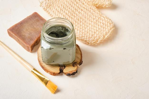 Голубая глина в стеклянной банке на деревянной подставке, бежевый фон, копировальная щетка для мыла какао и мочалка